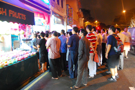 Migrant Workers Watching the CNY Program on TV in the Street