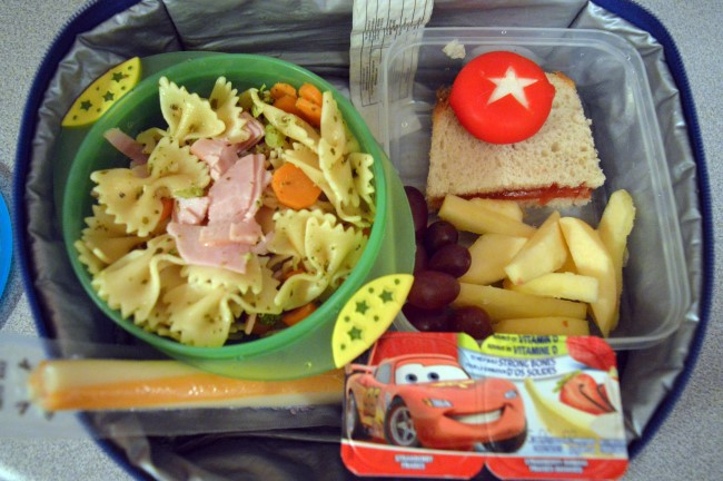 Pasta, carrots, broccoli, ham and pesto sauce / Mini Babybel cheese / Strawberry jam sandwich / Grapes / Apple / String cheese / Two yogurts / Apple sauce
