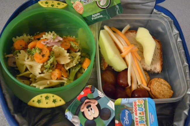 Pasta, carrots, broccoli, ham and pesto sauce / Strawberry jam sandwich / Grapes / Apple / String cheese / Two yogurts / Apple sauce