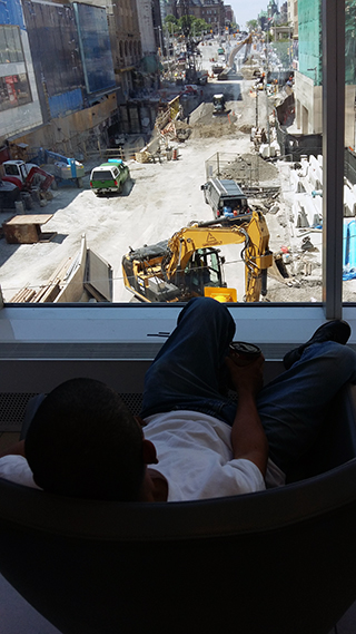 Man watching the construction site on Rideau Street on June 20 following the sinkhole disaster