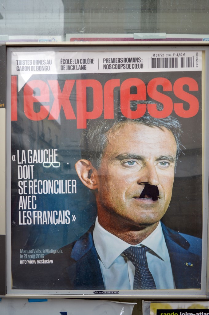 Cover of L'Express, a news magazine, with headlines on the Socialist Party. Hitler mustache added during the protest...