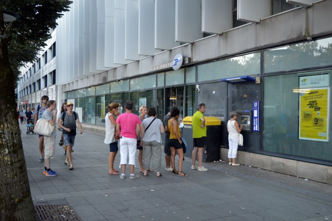 People queuing at a La Poste ATM