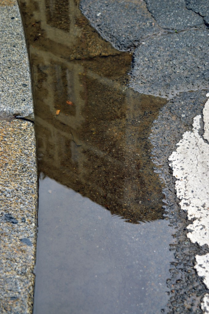 Reflection of the city in a puddle of rain
