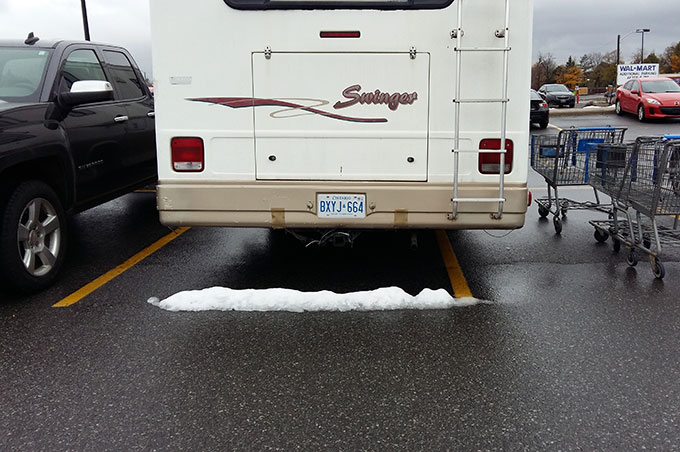 Snow under a RV on the supermarket's parking lot