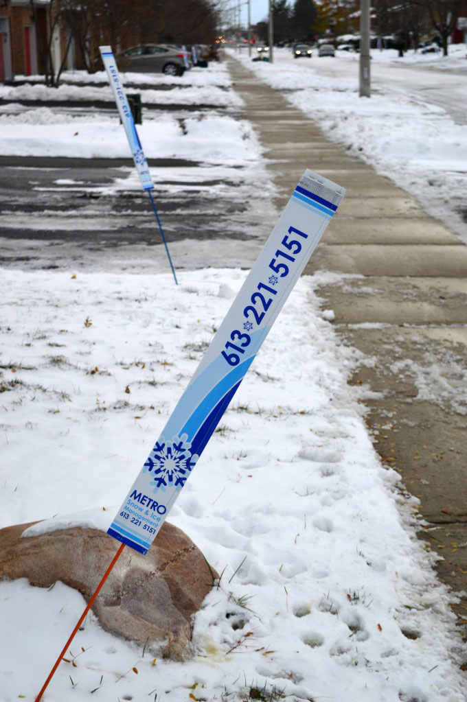 Signs flagging a house that signed up for a snow shoveling service
