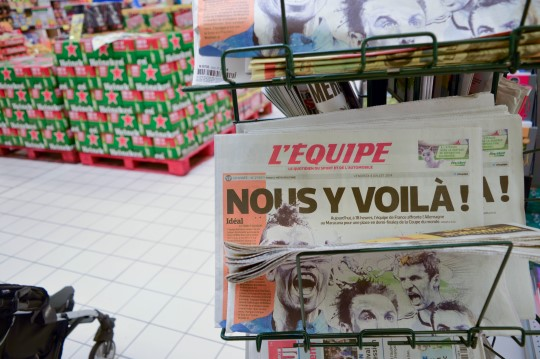 Beer Cases and L'Équipe at the Supermarket