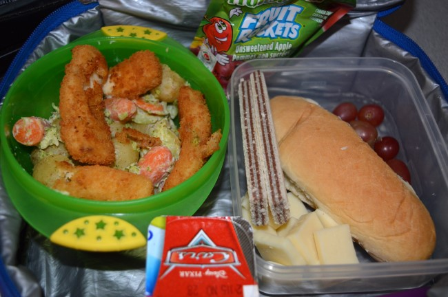 Steamed potato/carrots/broccoli with creamy sauce and breaded fish, peach jam sandwich, cheese, chocolate waffle cookies, grapes, yogurt and apple sauce