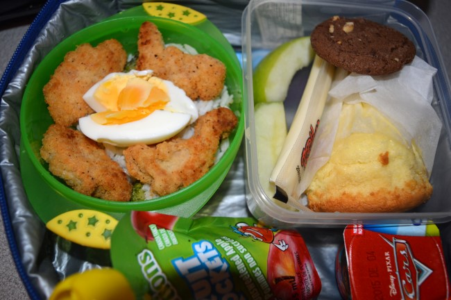 Stir-fried rice with broccoli and chicken nuggets with egg, string cheese, chocolate cookie, apple, vanilla sponge cake, yogurt and apple sauce