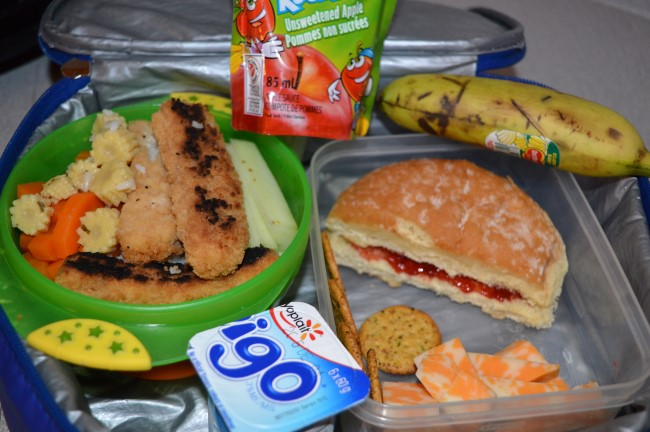 Steamed rice with carrots and cucumber and breaded fish, Italian bun with strawberry jam, crackers, cheese, banana, yogurt and apple sauce