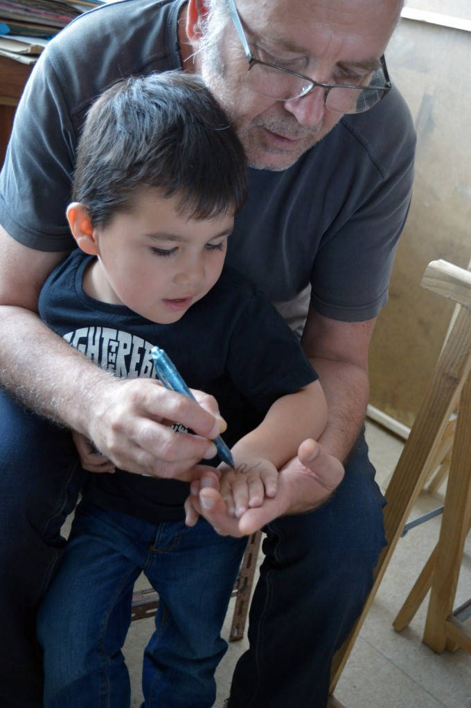 My dad drawing a monster on Mark's hand