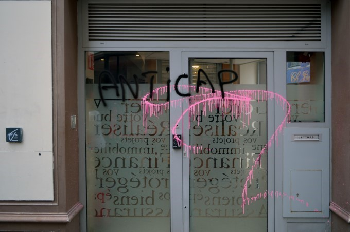 """Anti-capitalism"", graffiti on a store window"