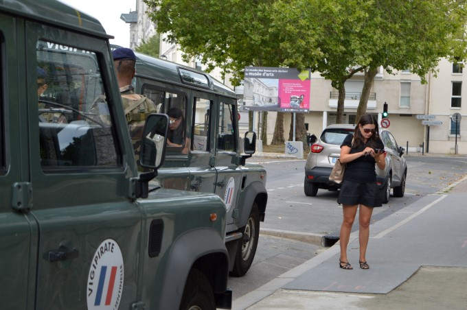 A woman checking her phone by a French military patrol, deployed as part of the Vigipirate Plan against terrorism