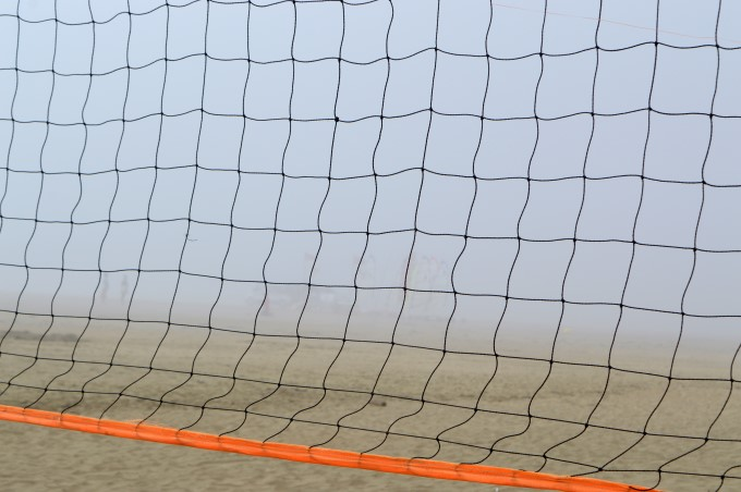 A basketball net in the mist on the beach