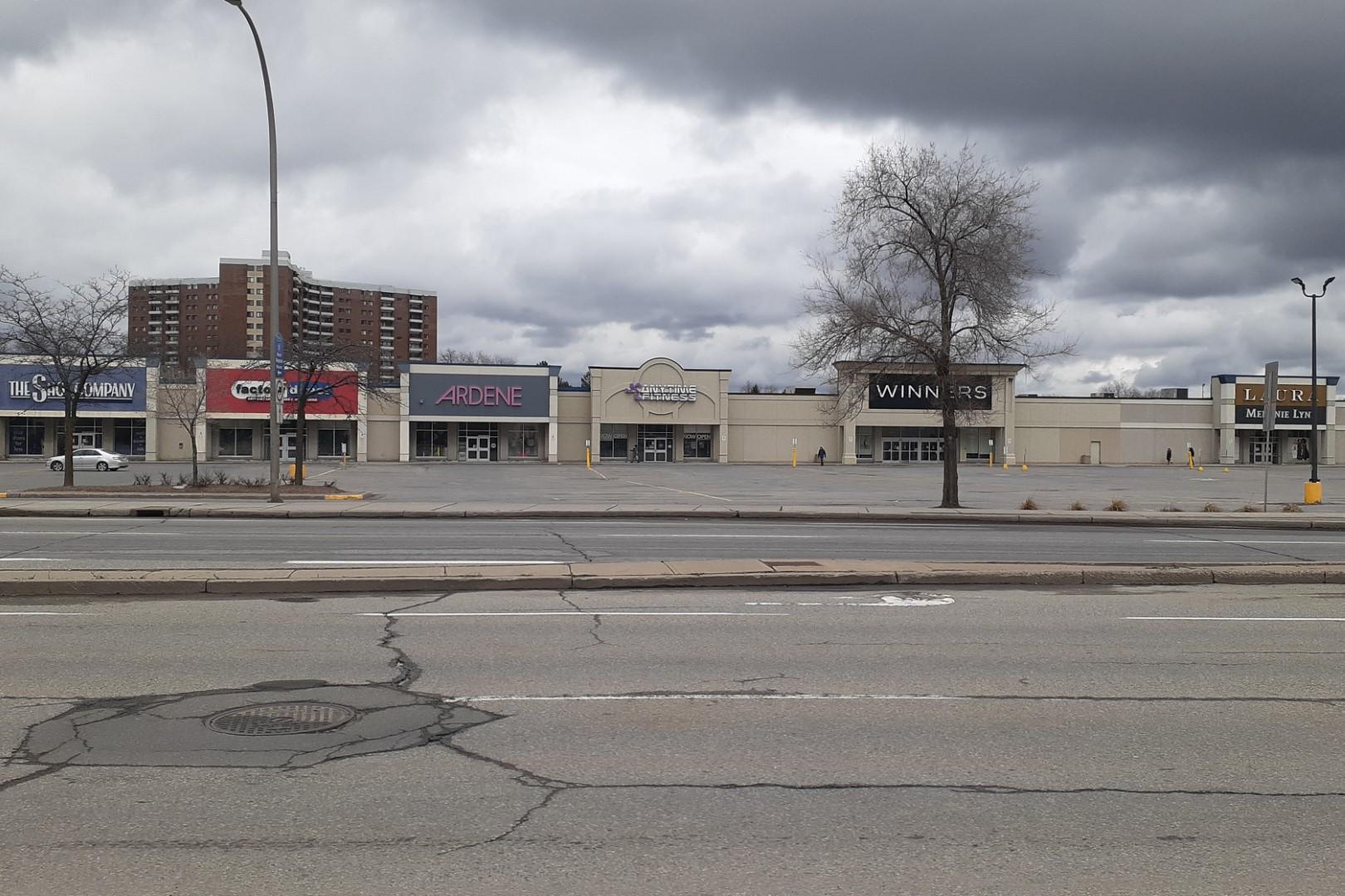 empty parking lot and closd stores, Merivale Road, Ottawa, April 2020